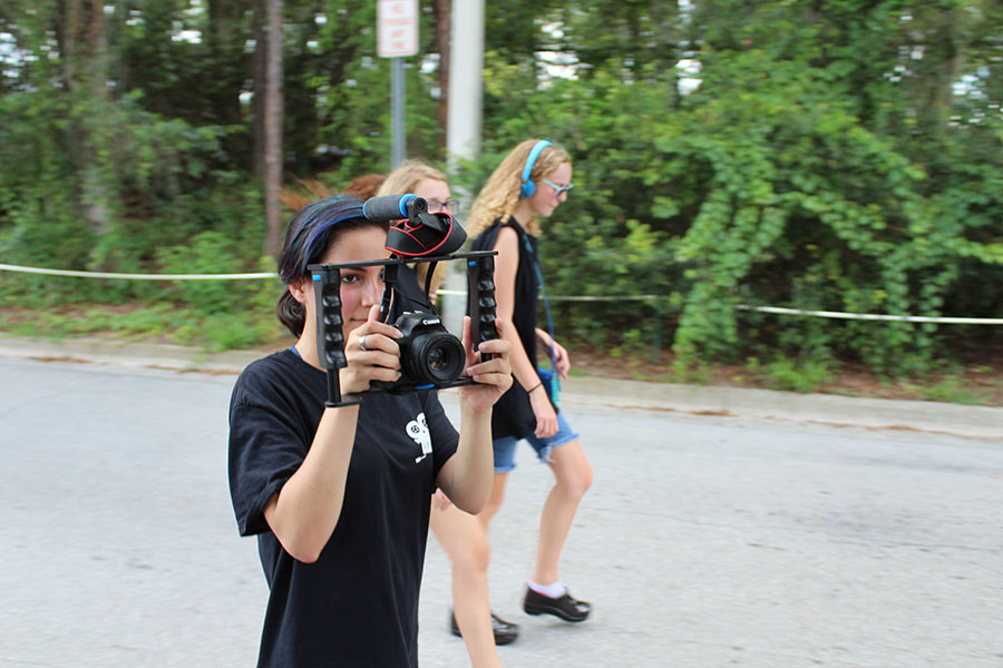 Senior Beatriz Arroch films the parade while walking with Film Club in the homecoming parade on september 7. A variety of clubs and activities, such as Film Club, and sports like Crew all showed their school spirit by walking in the parade.