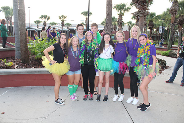 A group poses together prior to the Fat Tuesday theme day voting near the amphitheater as they prepare to parade on the stage. The group then participated in the costume voting and walked across the stage.