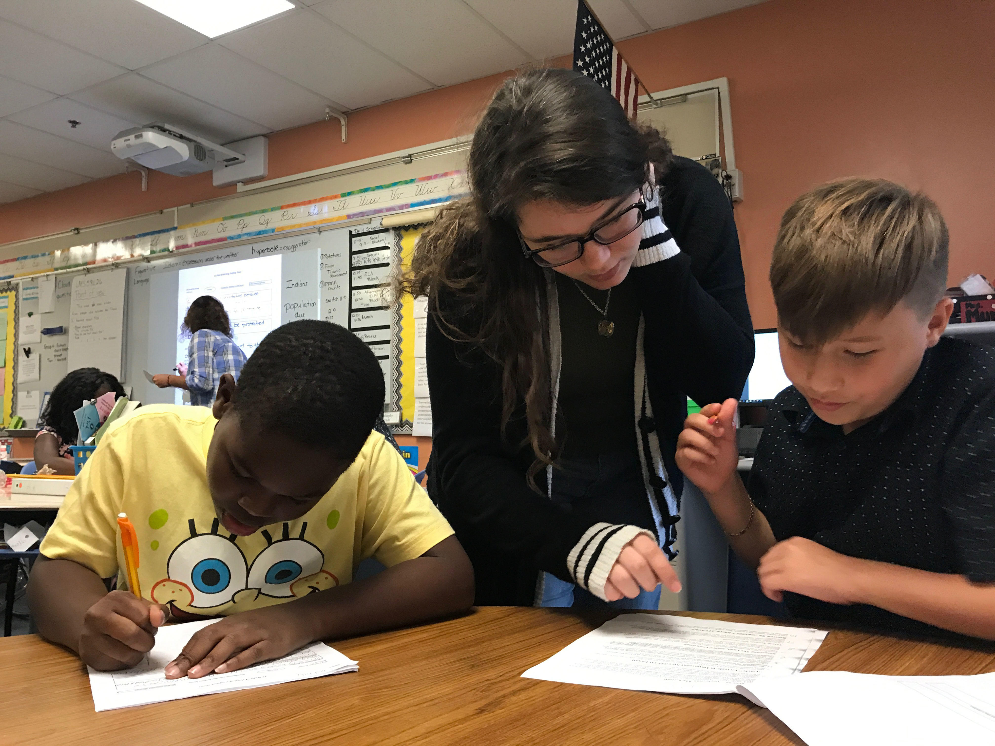 On Tuesday, Oct. 17, during tutoring at Forest City Elementary, junior Emma Murphy helps students A'kai Wallace and Jaiden Stokes with their reading packet. Emma spent over an hour helping the students at after school tutoring.
