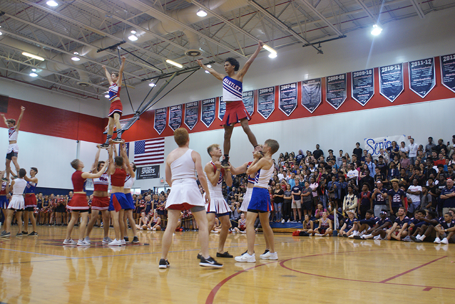 Senior powderpuff cheerleaders execute stunts on Thursday, September 28 in the main gym. They performed stunts similar to those that the cheerleaders engaged in.