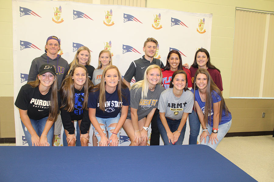 A group of Lake Brantley Athletes gather together and smile after signing the National Letter of Intent in the Community Room on Early Signing day. Family members, friends, and coaches watched as the athletes commit to where they will continue their athletics while furthering their education.