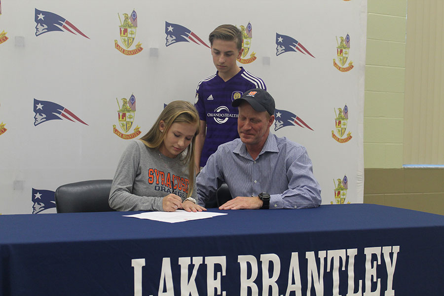 Senior Lauren Sniffen signs early to Syracuse University in the community room on November 8 with her family members. Signing to Syracuse means attending the school and being on their crew team.