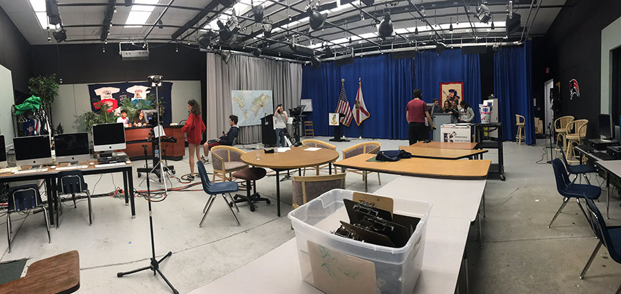 A panoramic shot of the television production studio at the start of the morning live show. The anchors are sitting patiently waiting for their cues to know when they can start to talk.