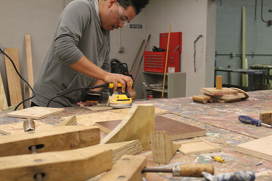 Senior Antonio Marquez sands wood in order to construct his assignment during his Building Trades and Construction Design Technology class on February. 7. Students build a variety of items, from toolboxes and stools to fuse ball tables.