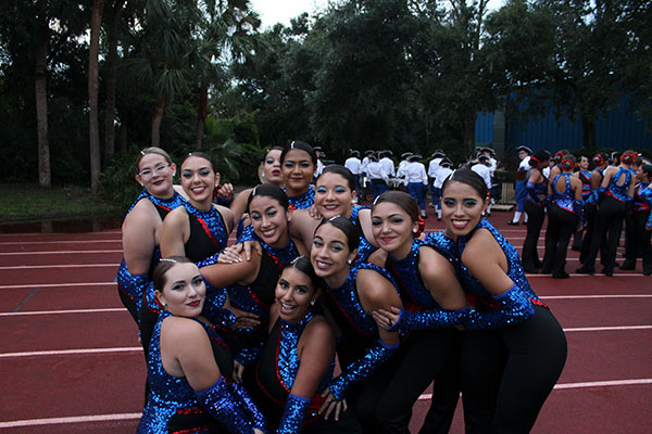 The dancers pose for a photo during their halftime show preparation where they stretch and practice parts of their routine. The football game against Hagerty High School took place on Friday, Aug. 24 on the Tom Storey Field, with the Patriots winning with a score of 35-17.