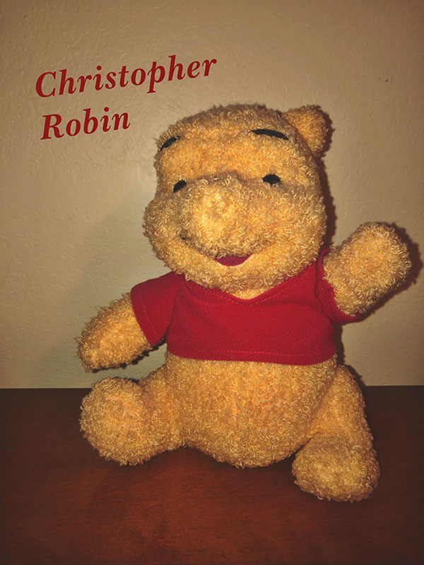 An+old+Pooh+Bear+stuffed+animal+is+posed+on+top+of+a+table.
