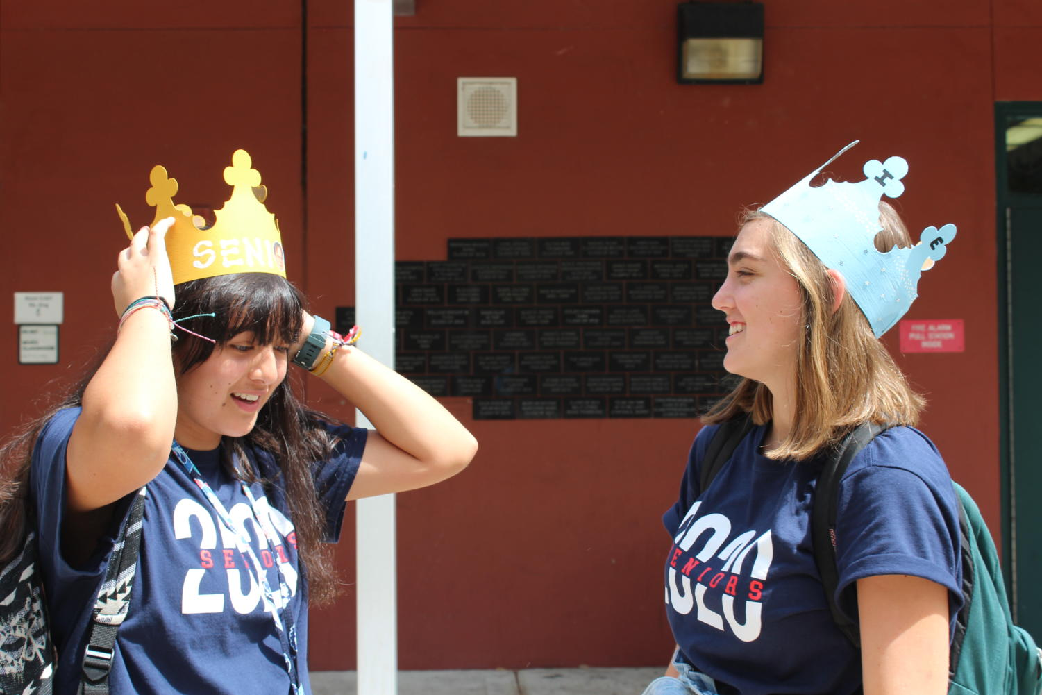 Katie Noonan laughs while Rachel Narvez fixes her crown to take a picture on Friday, August 16. Both girls painted their crowns to customize them and then wrote 'senior' across them, a design that has proved very popular this year.