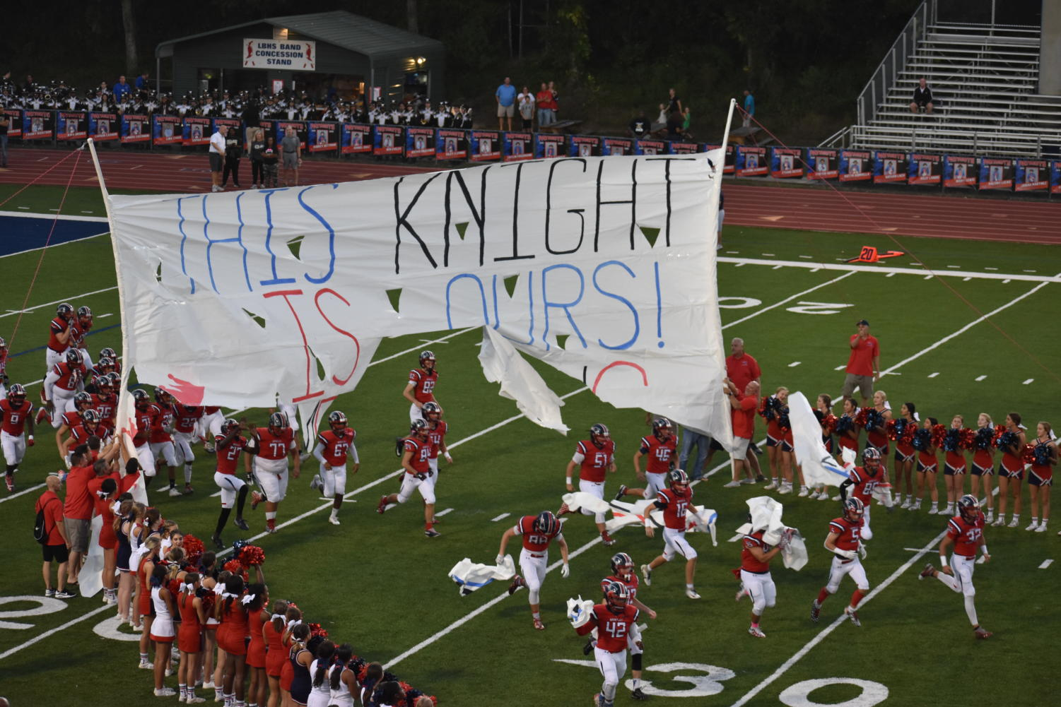 On Friday, Oct. 11, the varsity football team tears through the homecoming banner as they begin their game. The game was the first on the newly re-turfed Tom Storey Field.