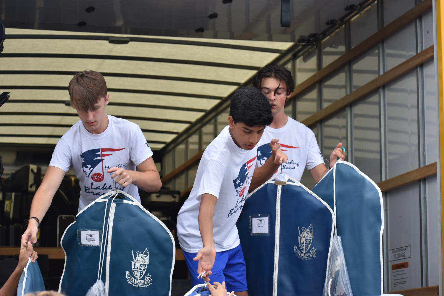 Students apart of the bands loading crew help unload the uniforms for the Lyman football game. During away games the band loads and unloads trucks of equipment, uniforms and instruments in order to perform at halftime.  Photo provided by: Angelina Jonkaitis