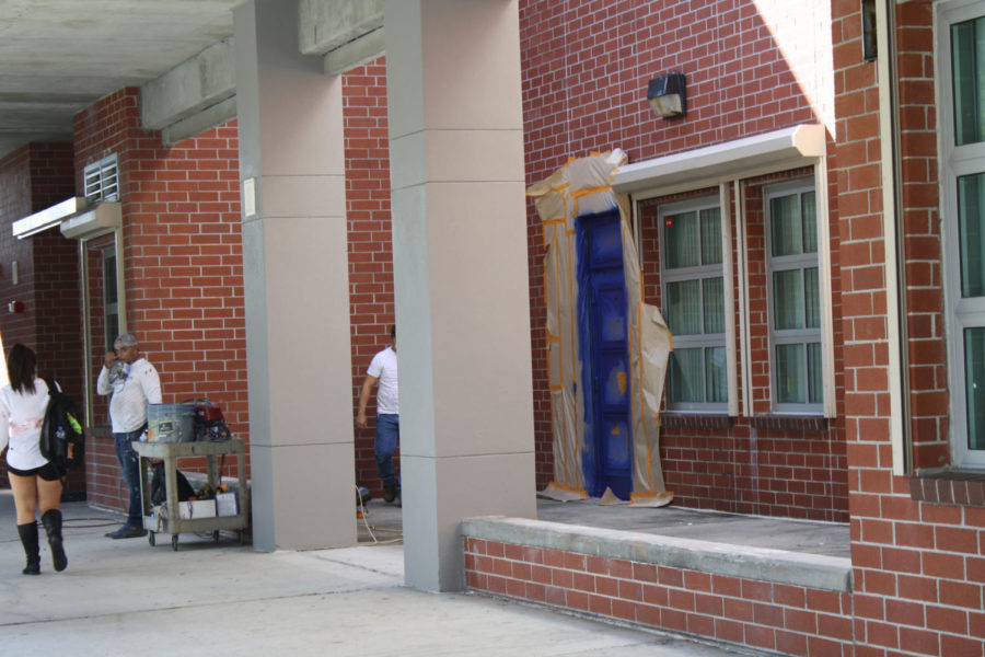 The staff hired to paint the school puts finishing touches on the now blue doors. Columns and the exterior of the building are also being repainted a steel grey color.