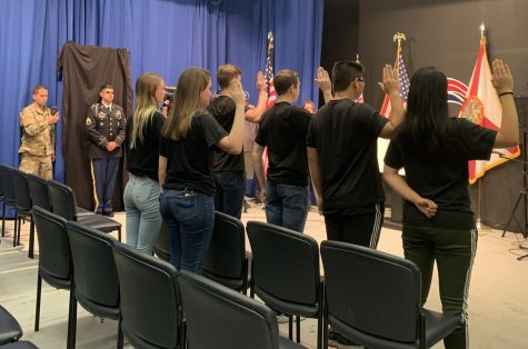 Six seniors from various Central Florida high schools hold their right hands up as they recite the United States Army Oath of Enlistment. One such student was senior Linsey Alexander, who plans to become a paratrooper.