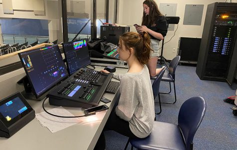 Sophomores Laura Howell and Ashley Welch play with the sound- and light boards on a set building work day.