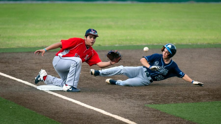 "During the game against Dr. Phillips High School on March 4, freshman Jordan Sanchez slides to catch the ball from the catcher to tag out the runner.  ""It's a great feeling to know when you are helping your team out in any way, shape or form,""  Sanchez said."
