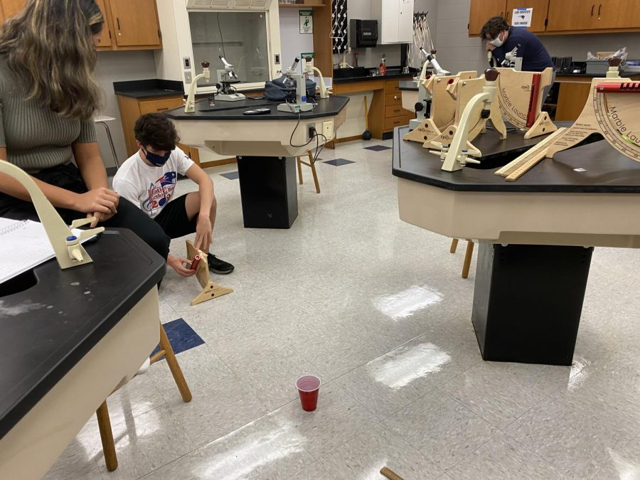 "Junior Elijah Huyck prepares to launch a marble into a cup during Stephen McGovern's fourth period AP Physics class. ""Basically, this lab was a real world application of the formulas we were learning in this class,"" Huyck said. ""The goal was to use the formulas we had learned to predict the outcome of a real world scenario."""