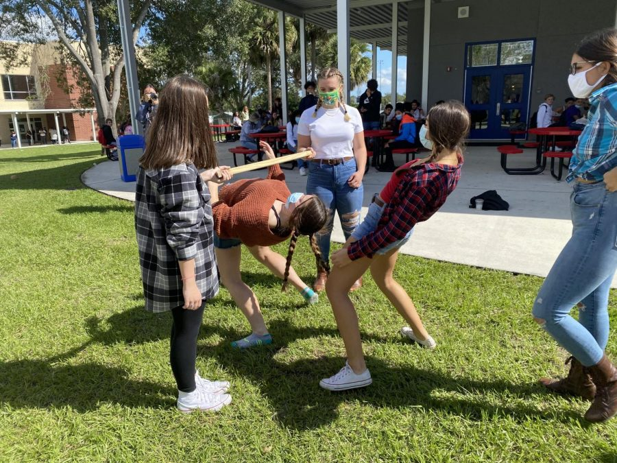 Seniors Emily Kirsch, Ashlynn Millis, and Veronica Vera participate in the limbo competition at C lunch on Wednesday, Nov. 4. Kirsch, Millis, and Vera are all Leadership students, and helped take the time to set up various festivities for students to participate in throughout the week.