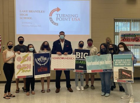 "Members of the Turning Point United States of America (TPUSA) club stand with guest speaker Matt Morgan on Feb. 19. ""Our club leader has lots of connections and Matt Morgan was one of them and she was able to get a timeframe for him to come in,"" junior Morgan  Schinneman said. ""He went more in-depth with what he did as mayor of Longwood and how he got into politics."""