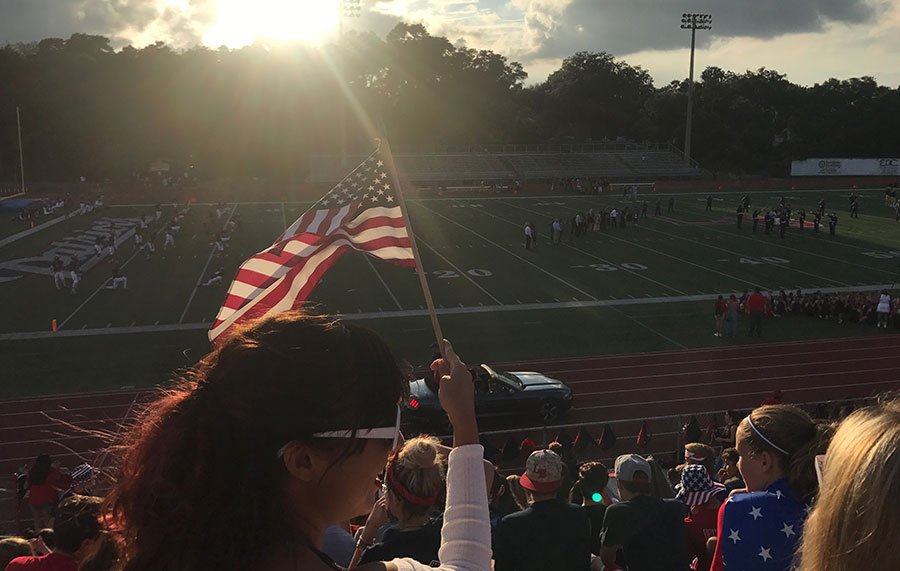 Sophomore Aurora Jimenez shows her school spirit by waving an American flag in the student section of Tom Storey Field. While she has a growing understanding of the sport, she still had fun just socializing in the stands and taking part in the excitement of the game.