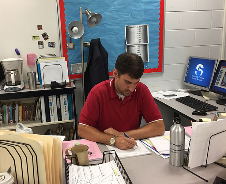 """New to the school, U.S. history teacher, Michael Jaycox, works at his desk during his fifth period plan. """"I will do whatever it takes to make a really good lesson, if I volunteer to do something I'm going to go full-toe and I'm going to put everything into it I can,"""" Jaycox said."""