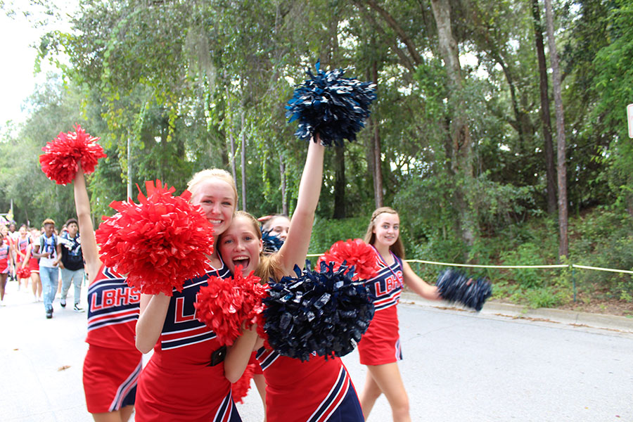 """Junior varsity cheerleaders and sophomores Lexee Yonke and Riley Hintze shake their pom-poms with pride as they walk with the class of 2020 in the homecoming parade on September 7. """"It was my first time walking in the parade and I had a great time because I got to see my classmates and represent my class,"""" Yonke said."""