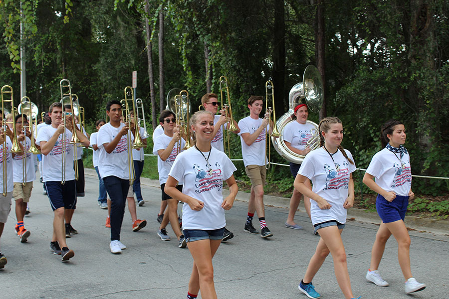 """Members of the Lake Brantley Band march in the homecoming parade while playing the fight song. """" It is an exciting experience because you get to see the elementary students from Forest City who look up to you,"""" Sophomore and trombonist Jeffrey Glatting said. """" It is lively because the whole school is participating."""