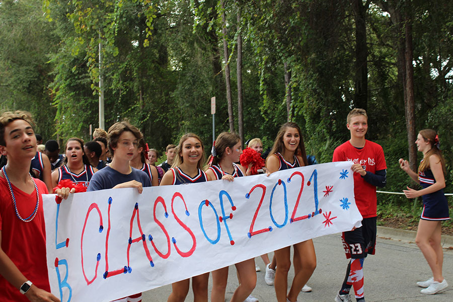 Students from the class of 2021 showed pride with a banner to represent their class while walking in the homecoming parade on september 7. Student council members holding the sign brought their class together in addition to making the freshman class float.