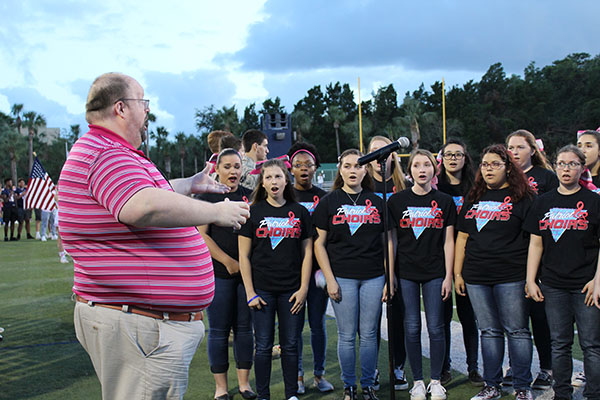 Carlton Kilpatrick conducts the spectrum chorus as they perform the national anthem at the Oviedo football game played at the Tom Story field on Friday Oct. 20. The spectrum group is the highest group of  chorus students at Brantley.