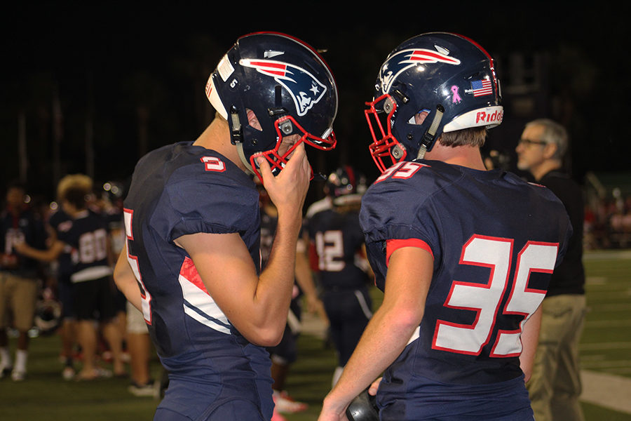 Senior Will Pikalow and junior Jett Boss discuss their last moves at the Tom Storey Field as the end of the game approaches on Friday, Oct. 20. Lake Brantley won with a score of 49, beating Oviedo by 21 points.