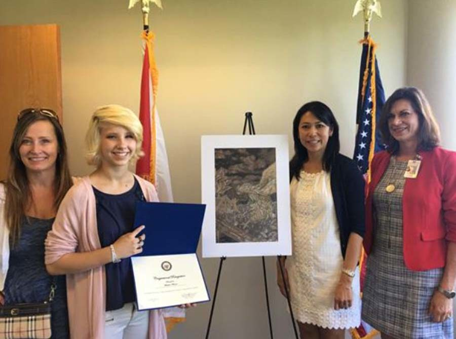 """Madeline Wheaton poses with her winning artwork, entitled 'Desolation' alongside Julia Wheaton, Congresswoman Stephanie Murphy, and Kathryn Farmer. """"We went over to Congresswoman Stephanie Murphy's office in Orlando and they had a ceremony where they took some photographs of her receiving the award from Congresswoman Stephanie Murphy,"""" Farmer said."""