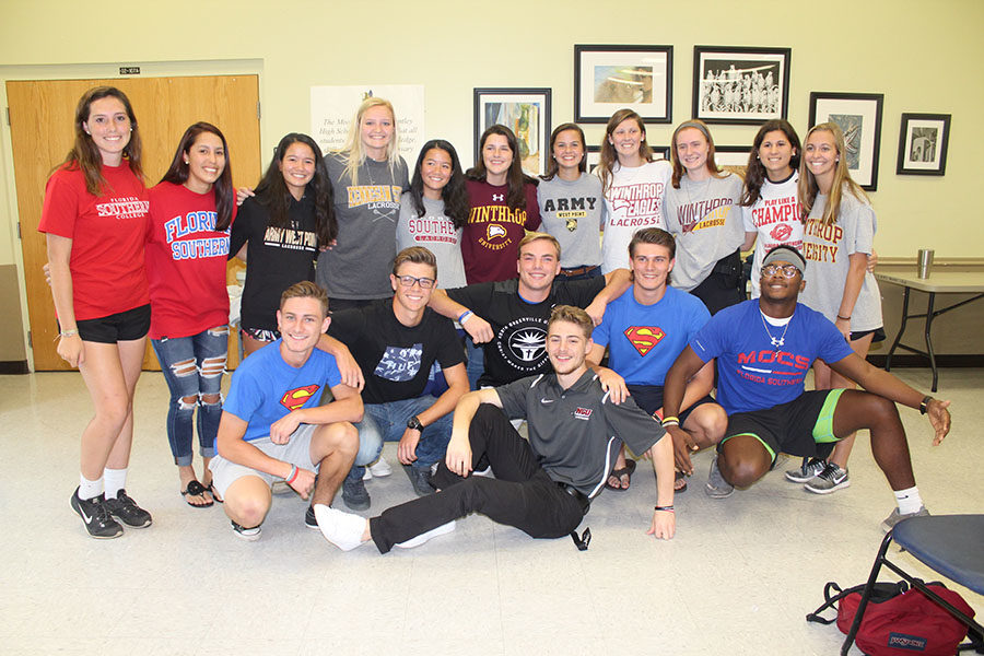 Senior athletes pose after signing their National Letter of Intent to the schools they plan to go to. Signing the letter creates a commitment between the athlete and the school, ensuring that the student will play their sport at the school they committed to.