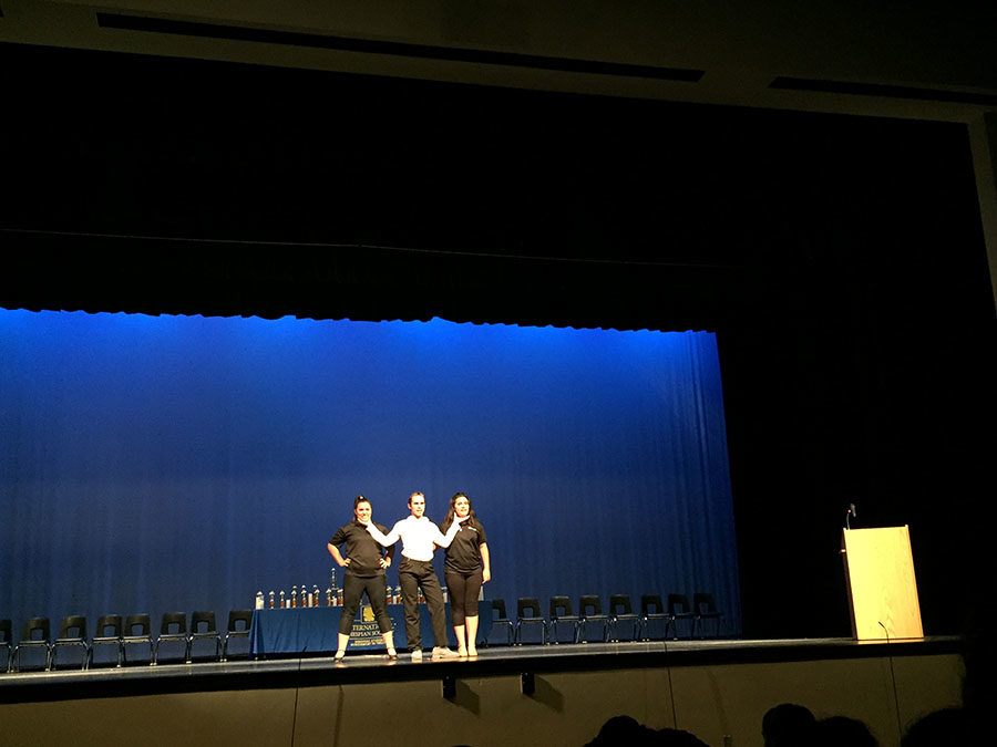 """During the District Competition closing ceremony on Saturday, Nov. 18, seniors Alex Iacuzzo, Francesca Natal, and Nicole Natal perform their small group musical. They sang and choreographed Cabaret's """"Two Ladies,"""" which won the award for Best in Show, the highest ranked in the small group musical category."""