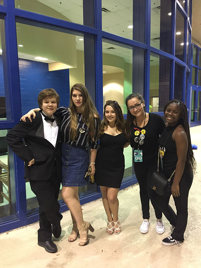 """Following closing ceremonies on Saturday, Nov. 18, """"Tracks"""" stage manager junior Bridget Froemming and tech crew members sophomore Jacob Shoemate, senior Paige Norman, junior Kaylee Savannah, and sophomore Destiny Spencer get together to celebrate the success of the One Act. Troupe 2888 was awarded a trophy for Best Crew for a One Act Play by the Districts judges."""