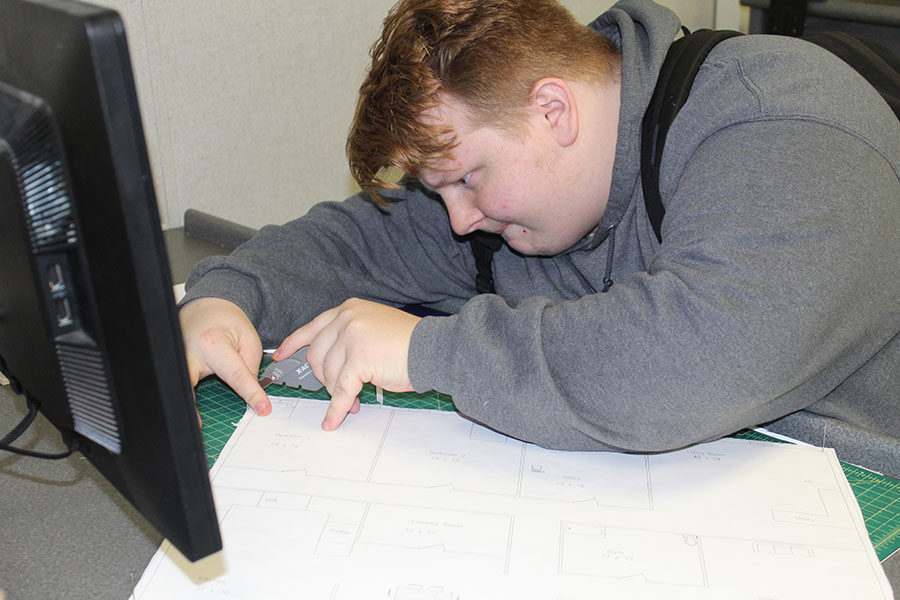 """Senior Jacob Gillette measures and trims foam to create a 3D housel based on his design in his 5th period Drafting Class on January 18. """"I'm cutting out the model to my floor plan to precision,"""" Gillette said."""