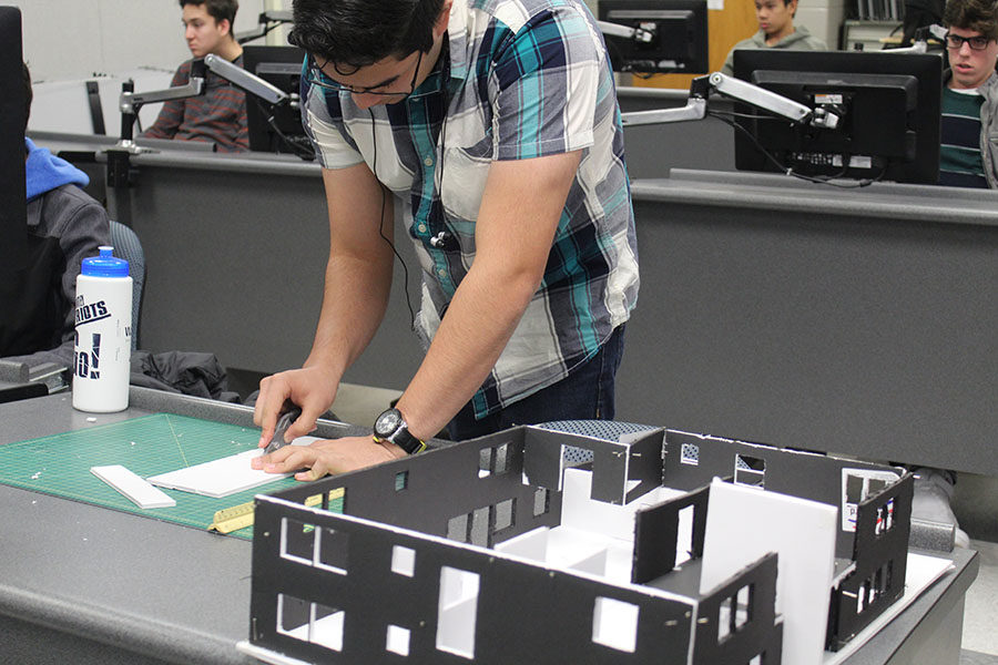 """Senior Gabriel Maisonet measures and slices foam in order to build a model house in his 5th period Drafting Class on January 18. """"I am making a house out of the 3D model that I designed,"""" Maisonet said. So far it's taken me about two weeks."""""""