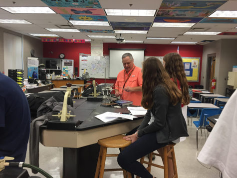 "Chemistry teacher David Duffy helps sophomores Emily Klingenberg and Marietta Long to lift up their crucible from the clay triangle during the ""Empirical Formula Lab"". The purpose of the lab was to expose students to oxidation techniques involving the careful use of Bunsen burners."