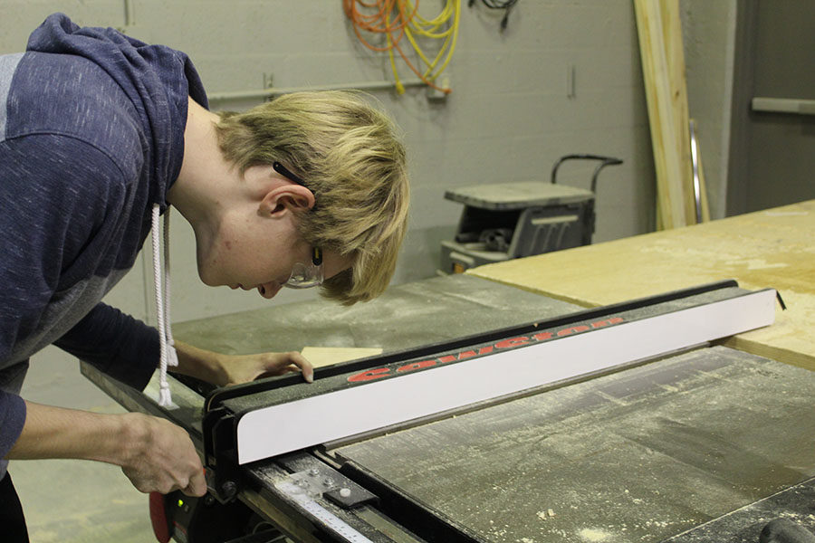 Senior Matthew Jodoin adjusts the measurements of a table saw in orders to precisely trim his materials in Robert Flanders classroom on February 7. A table saw is a tool with a circular blade placed directly under a table that is powered by an electric motor, which allows for a smooth and exact cut.