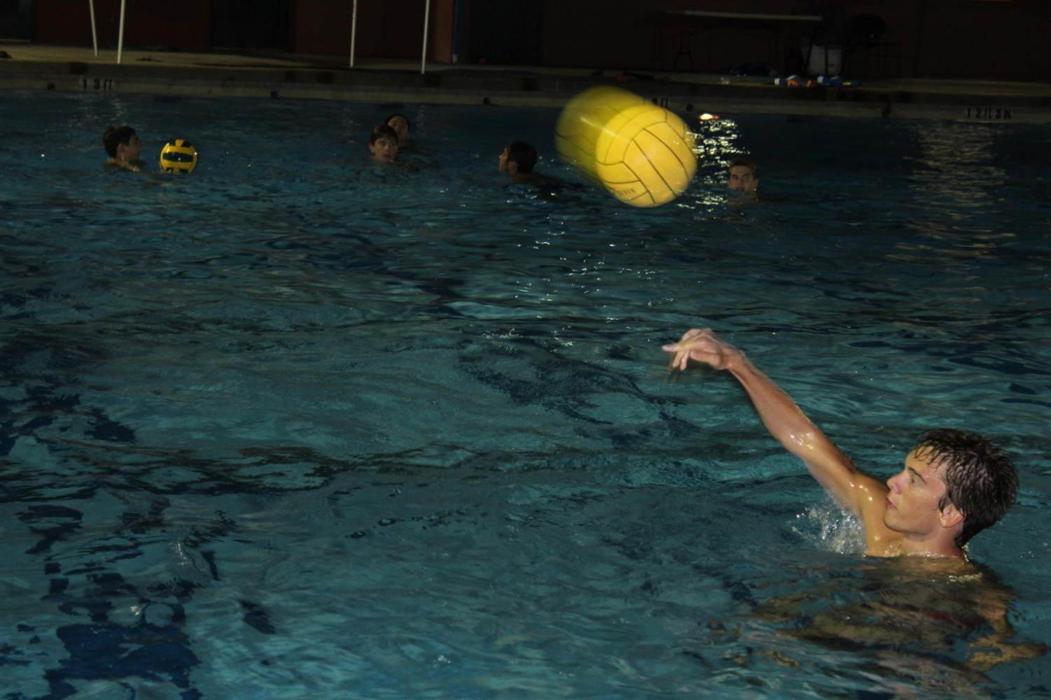 The+signature+bright+yellow+water+polo+ball+is+hurled+across+the+pool+to+Sophomore+Isaac+Benjamin.+While+attempting+to+catch+passes+players+must+also+tread+to+keep+their+heads+and+shoulders+above+the+water.+The+constant+movement+is+one+of+the+reasons+why+water+polo+is+considered+one+of+the+most+challenging+sports+of+all+time.+
