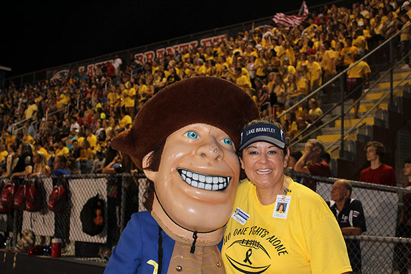 Patriot Pete and Principal Dr. Trent Daniel pose for a photo in front of the crowd displaying their yellow-out gear in order to support B11, a rare form of cancer afflicting Dr. Daniels son, Britton. The football game against Hagerty High Dchool took place on Friday, Aug. 24 on the Tom Storey Field, with the Patriots winning with a score of 35-17.