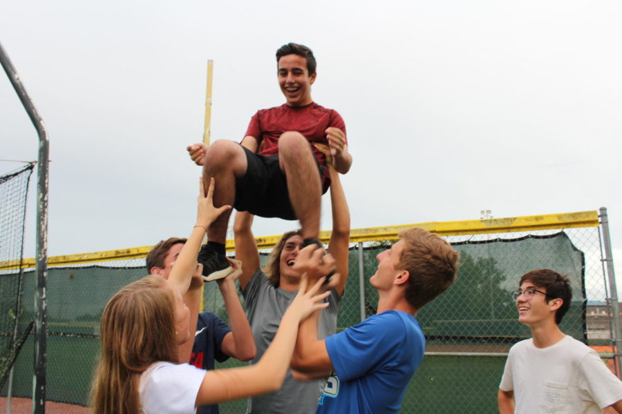 Junior Ben Evelev is held up by powder puff cheerleaders as they attempt to stunt at practice on Monday, August 27. This was the first powder puff practice so the cheerleaders were still deciding which boys would fly and which ones would be bases.