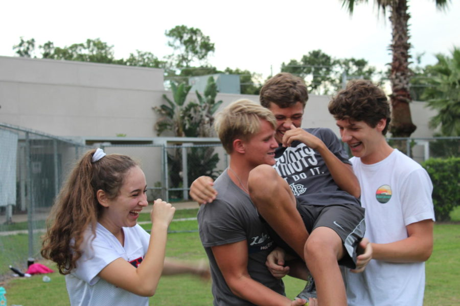 Junior Carson Yore is caught by Chris Kennon, Ryan Nolan, and Brianna Cullari after they stunt with him on Monday, August 27. Yore was one of the boys chosen to be flyers for the halftime performance.