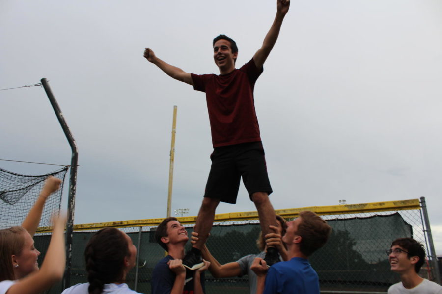Junior Ben Evelev flies in a half stunt while the cheerleaders celebrate on Monday, August 27. The Junior boys performed their routine for the halftime show during the powder puff game on Monday, September 17.