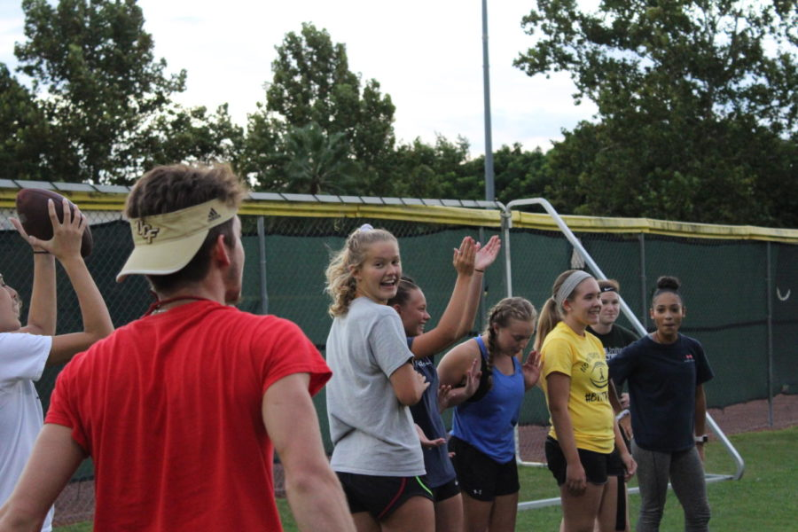Junior girls cheer for their teammates as they practice throwing and catching the football on Monday, August 27. There were three stations at the first powder puff practice that each taught the girls a different skill they would need for the game.