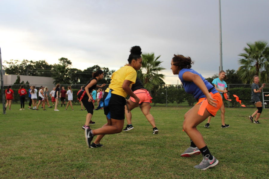 Juniors Anayansi Santiago and Aliyah Betancourt try to pull each others flag belts on Monday, August 27. The coaches told the girls to start lying on the ground and get up to grab their partner's belt when the whistle was blown.
