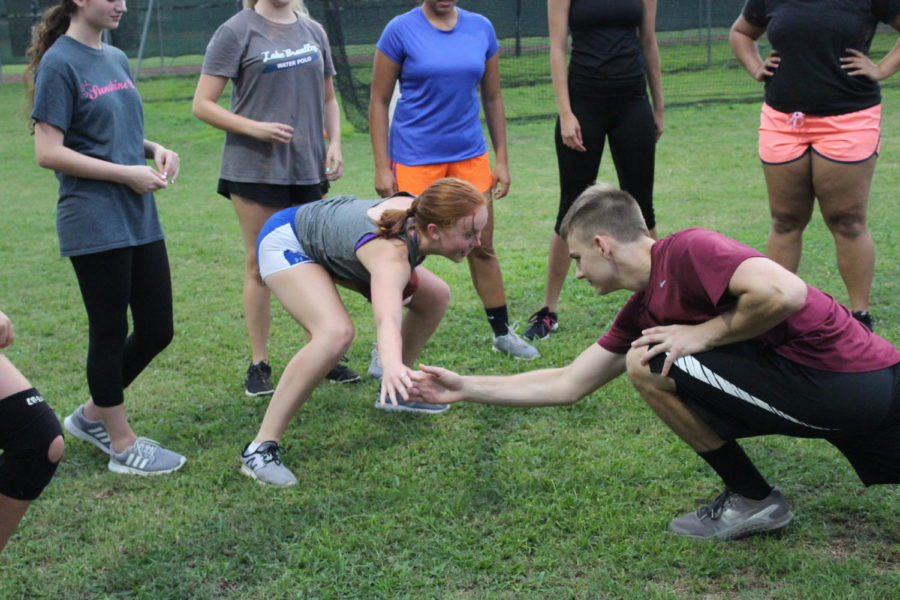 Junior Elliot Maier tests Grace Burke's balance as she practices a three point stance on Monday, August 27. A three point stance was used by the line-men and running-backs during the game.