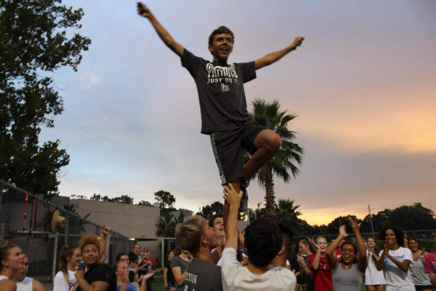 Junior Carson Yore performs a liberty while the junior powder puff participants cheer for him on Monday, August 27. This practice was held at the field outside Brantley South, the gym across the street from Lake Brantley.