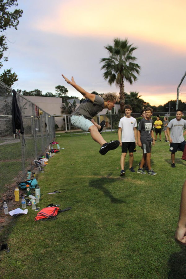 Junior Chris Kennon shows off his toe-touch on Monday, August 27. Because of his impressive jumps, Kennon was placed at the front of the triangle when the boys were jumping during their routine.