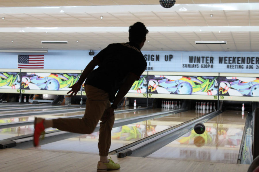 Senior Josh Singh watches the ball roll down the lane, at Oviedo Lanes on Monday, August 27, after he lets go. Many teams shout out chants to keep their bowlers energized.