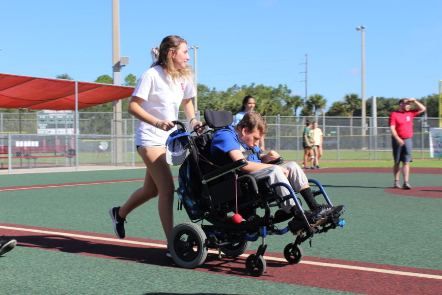 Junior Sara Vratanina wheels her buddy from home base to first after he hit the ball during Buddy Ball on Saturday October 20 at the Eastmonte baseball fields. Buddy Ball includes kids ages 5-20 and volunteers of all ages.