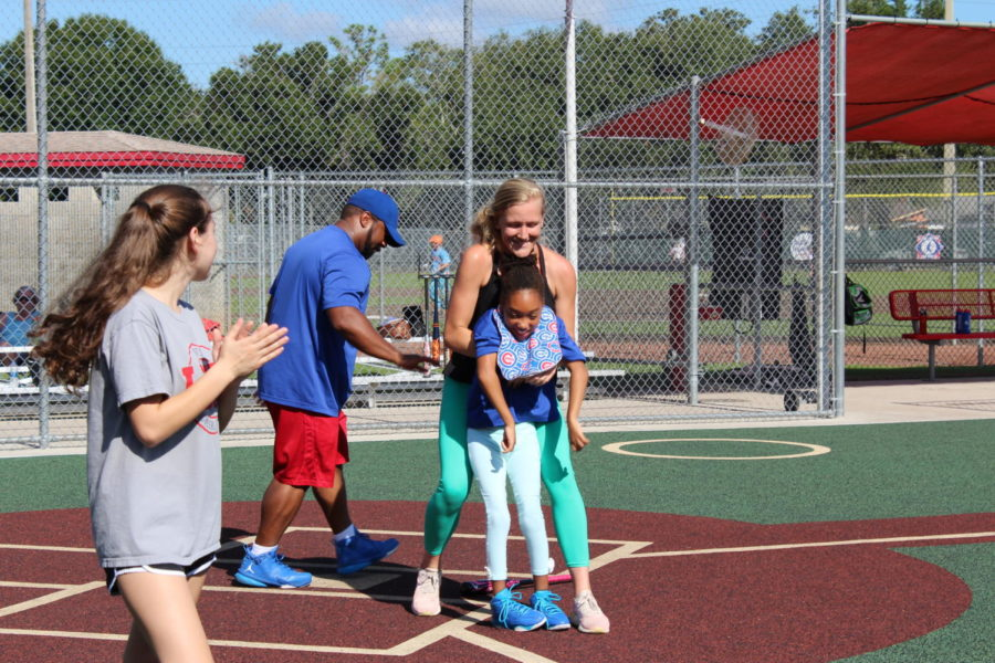Junior Brianna Cullari claps for a player and her mother as they hit the ball together, drop the bat, and run to first during Buddy Ball on Saturday October 20 at the Eastmonte baseball fields. While all Buddy Ball players are special needs, many are in a wheelchair as well.