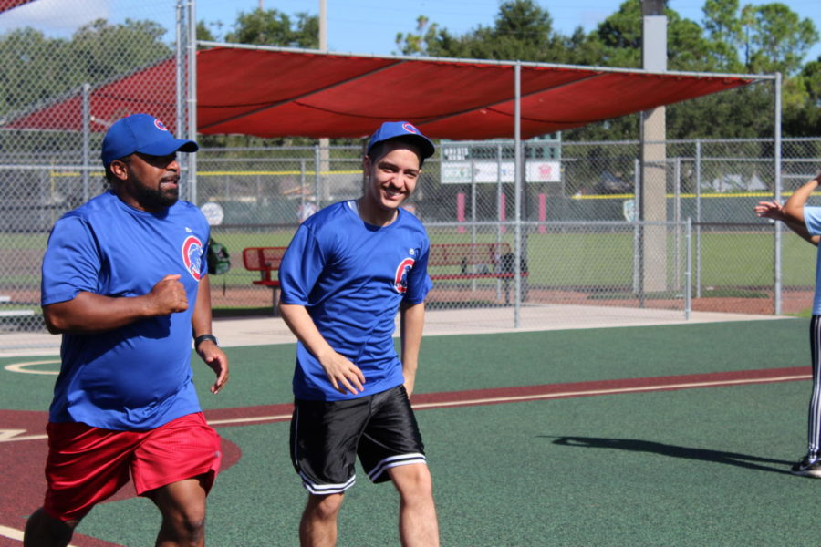 A player and his coach run to first base after the player has hit the ball during Buddy Ball on Saturday October 20 at the Eastmonte baseball fields. Buddy Ball focuses on engagement and fun, not points or accuracy.