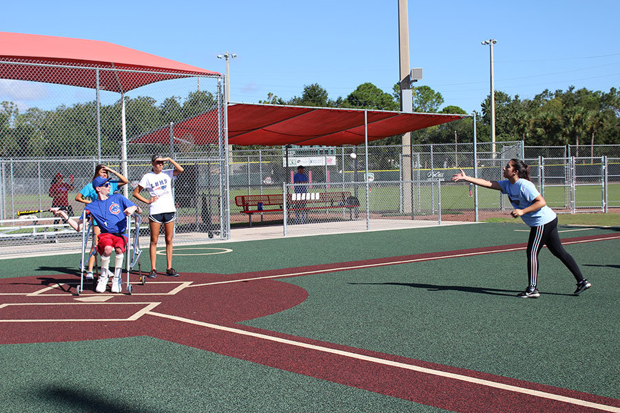 Juniors Madison Harris and Teddy Georgieva watch as a player waits for the pitch during Buddy Ball on Saturday October 20 at the Eastmonte baseball fields. One main job of the students was to wheel the players in wheelchairs to the bases.